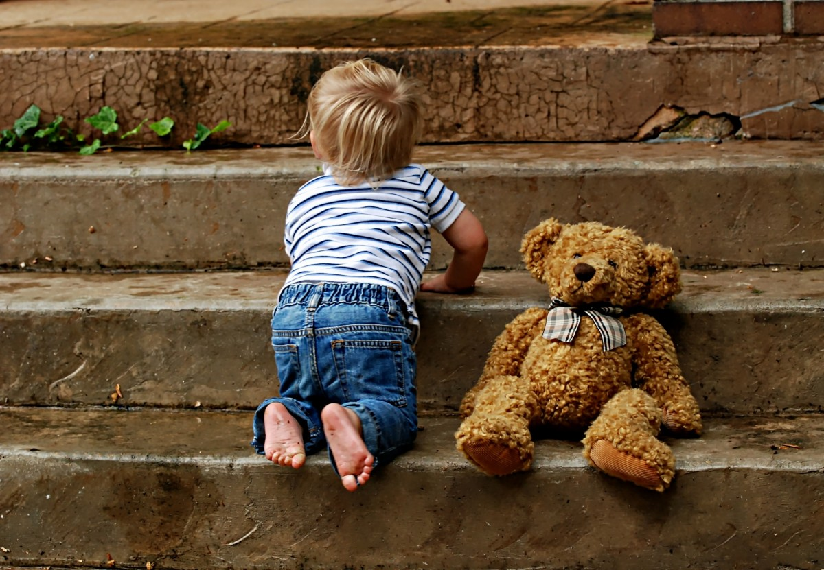 Boy with teddy bear on stairs